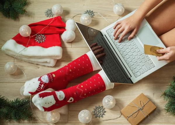 Girl shopping online for christmas presents with laptop computer on her legs credit card and christmas decorations top view min